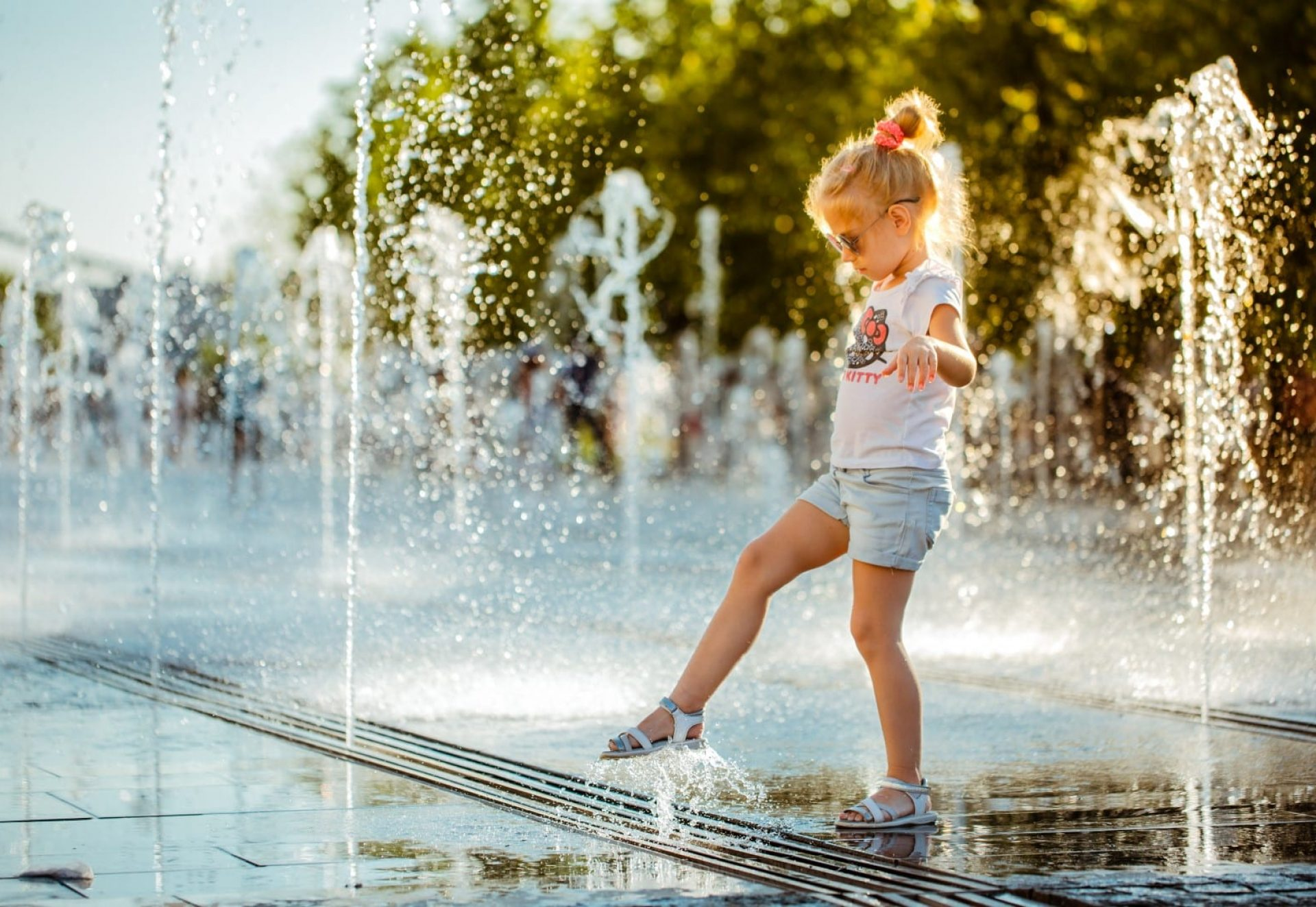 A little girl with her foot touches the water jet of a pedestrian fountain on the Crimean embankment in Muzeon Park.
