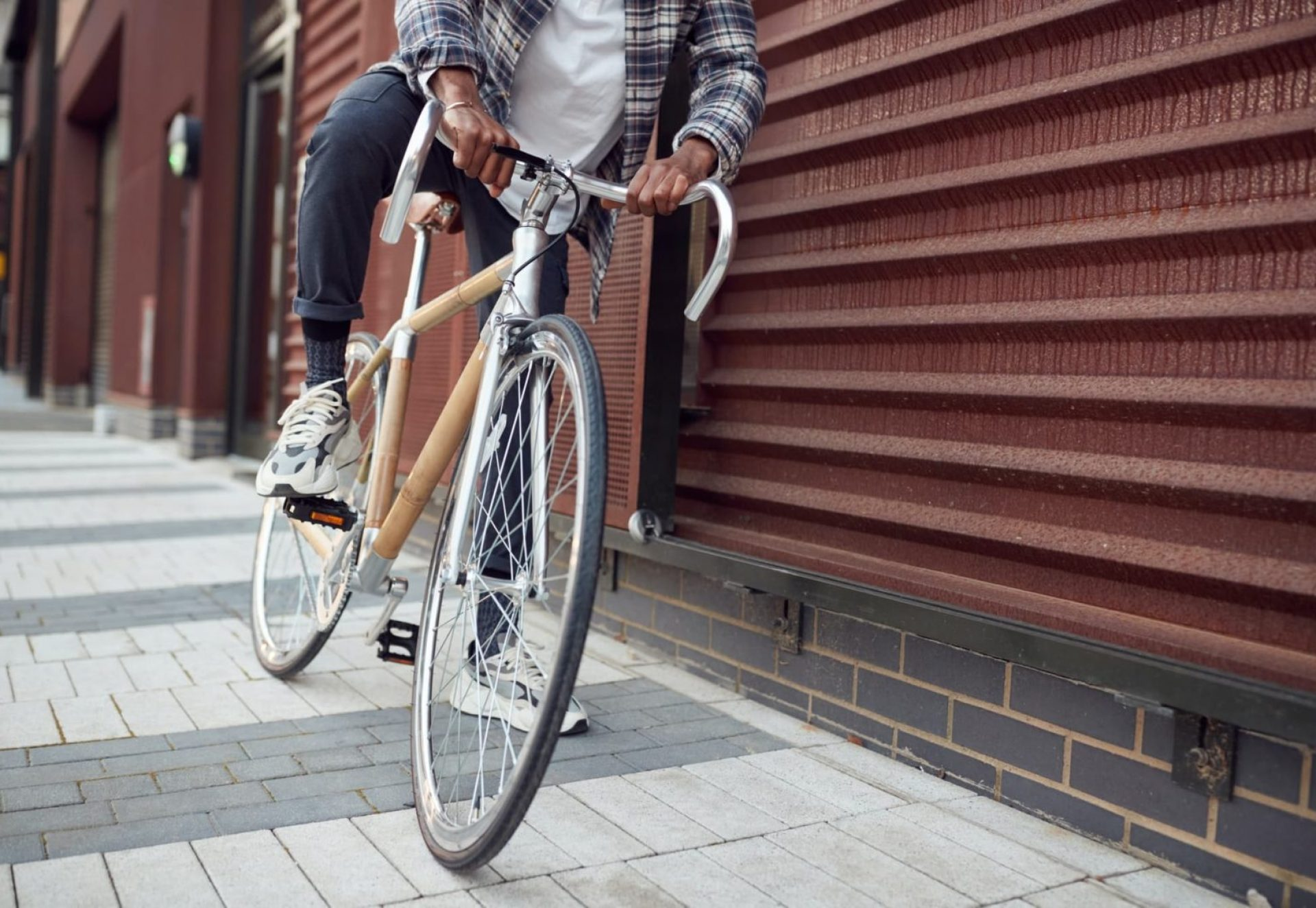 Close Up Of Man Riding Sustainable Bamboo Bicycle On City Street