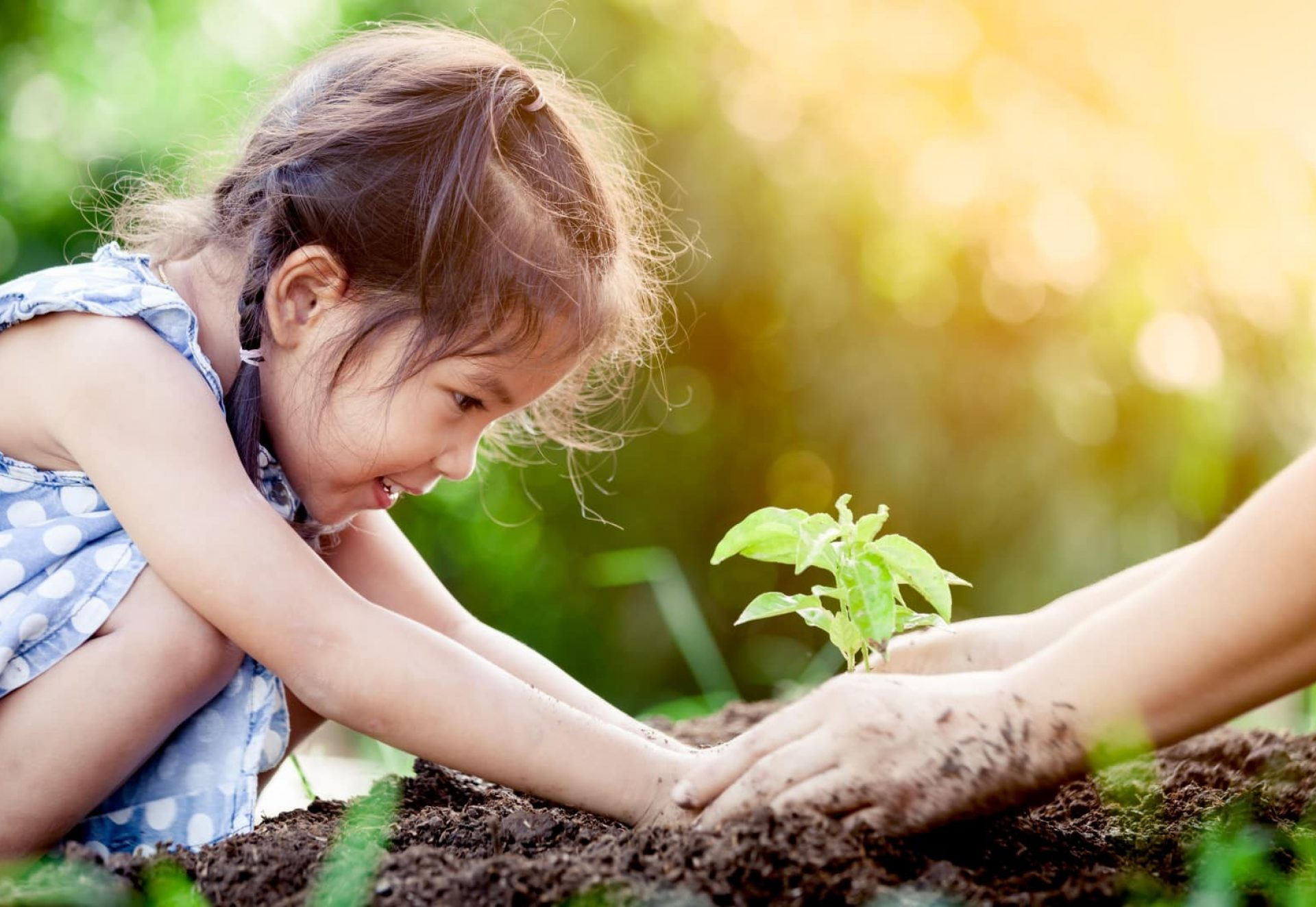 Petite fille asiatique et parent plantant un jeune arbre sur le sol noir ensemble comme concept du monde de sauvegarde sur fond de couleur vintage